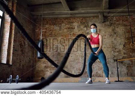 Young Woman Wearing Face Mask Exercising With Battle Ropes At The Gym. Strong Female Athlete Doing W