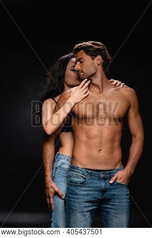 Seductive Woman Embracing And Kissing Young Man With Muscular Torso On Black.