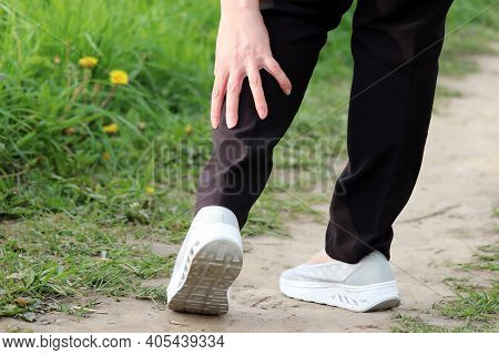 Ankle Sprain, Woman Grabbed Her Leg While Walking On A Nature. Concept Of Tired Legs, Injury On Runn