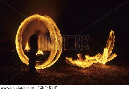 Scuol (engadine), Switzerland - February 4, 2017: A Man Spin A Fire Bal During The Hom Strom Day, Sc