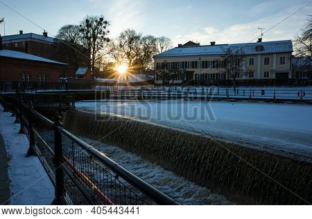 Vasteras, Sweden - January 15, 2021: Low winter sun shining in city, View of fauna passage on Svartan river, passageway allow fish freely migrate up river