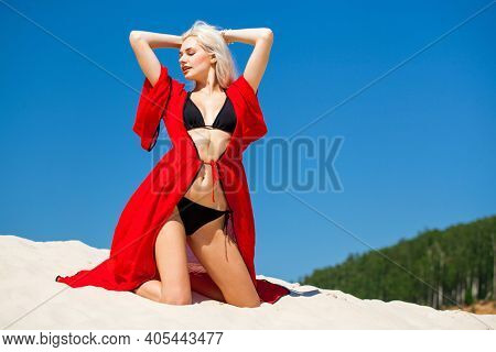 Full body portrait of a young beautiful blonde girl in black bikini and red tunic