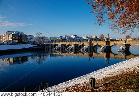 Gothic Medieval Stony Deer Bridge With Show, Riverbank Of The Otava River In Winter Sunny Day, The O