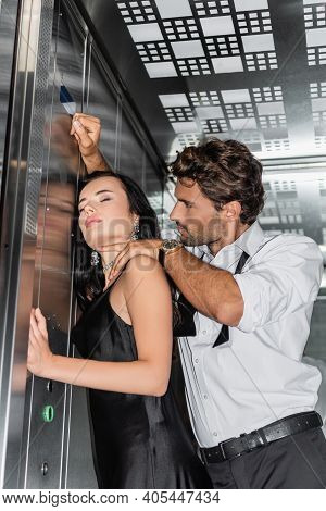 Elegant Man Touching Neck Of Sexy Woman While Seducing Her In Elevator.
