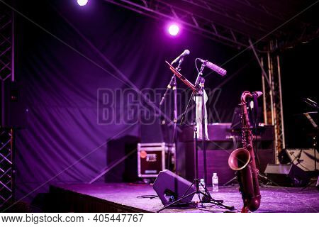 Saxophone Instrument On The Stage, Photo Close-up. Golden Saxophone Stands On The Stage Next To Othe