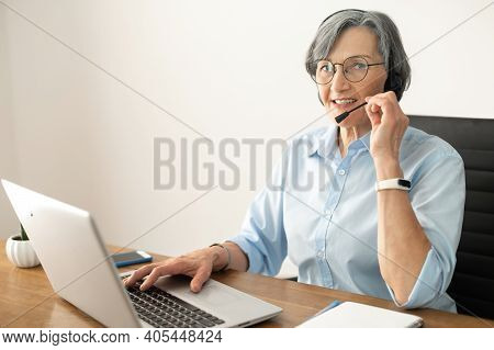 Senior Mature Female Gray-haired Call Center Operator Sitting At The Desk In The Home Office, Wearin