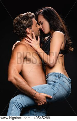 Side View Of Shirtless Man Holding And Kissing Passionate Brunette Woman Isolated On Black.