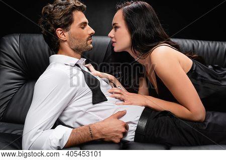 Side View Of Passionate Woman Seducing Elegant Man On Black.