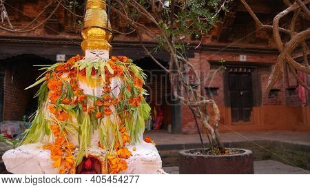 Statue In Yard Of Aged Oriental Temple. White Statue With Colorful Garlands In Stone Yard Of Buddhis