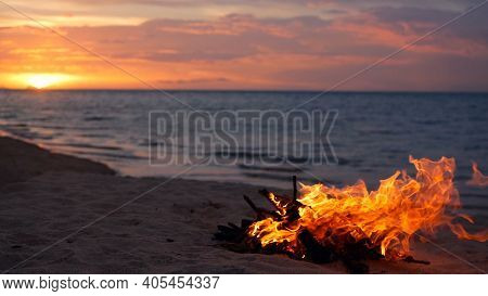 Blazing Campfire On Beach, Summer Evening. Bonfire In Nature As Background. Burning Wood On White Sa
