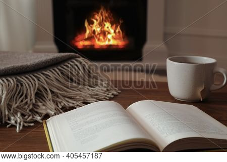 Cup Of Hot Tea And Book On Wooden Table Near Fireplace At Home. Cozy Atmosphere