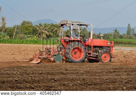 Red Tractor Plowing Groove In Field Thailand.