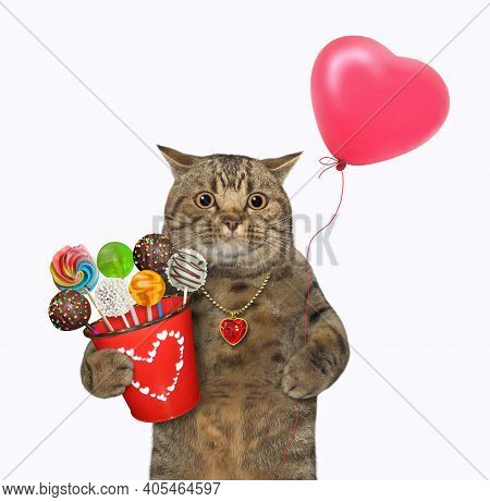 A Beige Cat Holds A Red Pail With Sweets And A Heart Shaped Balloon. White Background. Isolated.