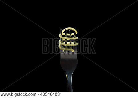 Spaghetti On A Black Background. Boiled Spaghetti On A Fork. Isolated Spaghetti