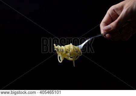 Spaghetti On A Black Background. Boiled Spaghetti On A Fork. Isolated Spaghetti. Male Hand Holding A