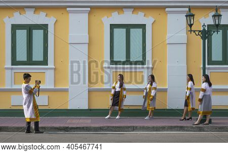 Bangkok, Thailand - August 29,2020 : Young Asian College Students Group In Graduation Gowns Are Taki