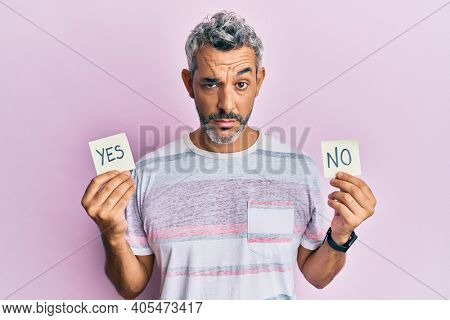 Middle age grey-haired man holding yes and no reminder skeptic and nervous, frowning upset because of problem. negative person.