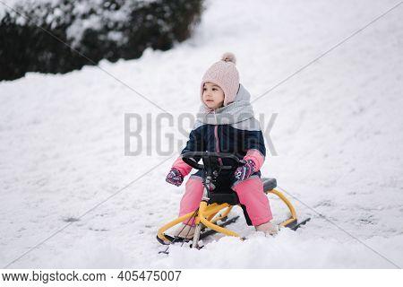 Little Girl Enjoy A Sleigh Ride. Kid Sledding. Kids Sled In Park In Winter. Outdoor Fun For Family C