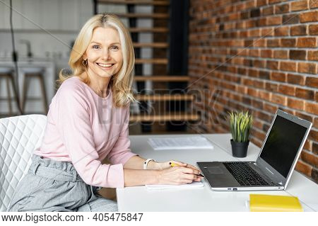 Enchanting Middle-aged Businesswoman Looks At Camera And Smiles. Close-up Portrait Of Charming Blond