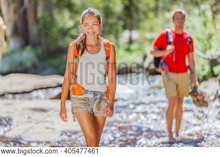 Hikers walking in forest crossing water stream holding boots hiking through Yosemite nature outdoors. Happy Asian girl and man in summer hike activity with backpacks.