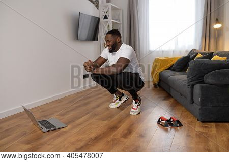 Handsome Young African American Is Holding His Body In The Squat Position, Getting Active While Isol