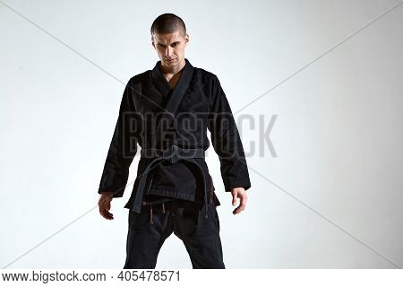 Sportive Frowning Man In Black Kimono For Karate Or Kudo On White Studio Background With Copy Space