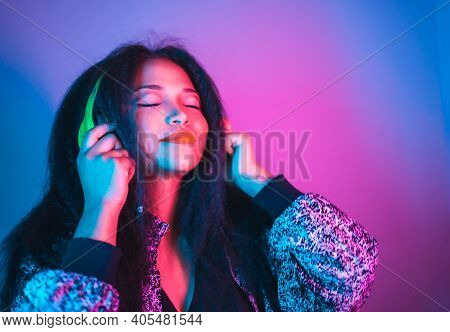A Vertical Closeup Of A Young Happy Hispanic Female Enjoying Music With Headphones And Dancing