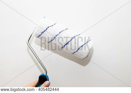 Male Hand With A Roller For Painting Walls. The Painter Applies Decorative Paint To The Wall.repair