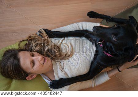 Young Woman Lying On Living Room Floor With Her Beautiful Black Shepherd Dog Lying On Her Cuddling.