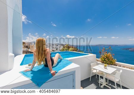 Young Woman On Vacation At Santorini, Women At The Swimming Pool Looking Out Over The Caldera Sea Of