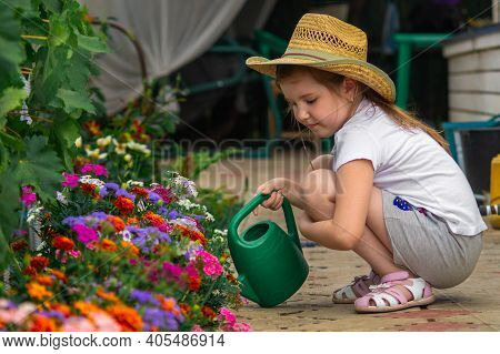 Lovely Little Girl In Straw Cowboy Hat, White T-shirt And Grey Shorts Outdoor In Garden Takes Care O