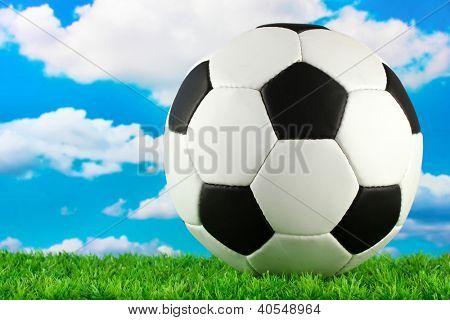 football ball on green grass, on blue sky background
