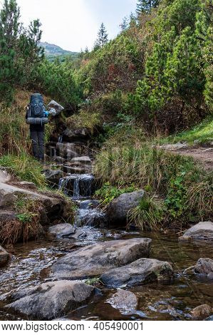 A Tourist With A Backpack Stands Near A Water Source. Tourist With Equipment. Vertical Frame.