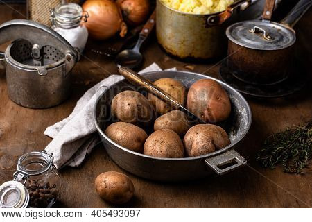 Raw Uncooked Potato In Old Vintage Pot. Rustic Kitchen Background