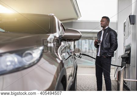 Handsome Young Bearded Black Man Having A Rest And Drinking Coffee To Go, While His Car Is Refueling