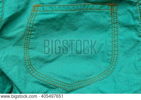 Green Texture Of Crumpled Fabric On Clothes With A Seam Of Yellow Threads On A Pocket