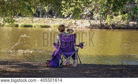 Mackay, Queensland, Australia - January 2021: Female Retiree Photographer Taking Photos Of Birds On