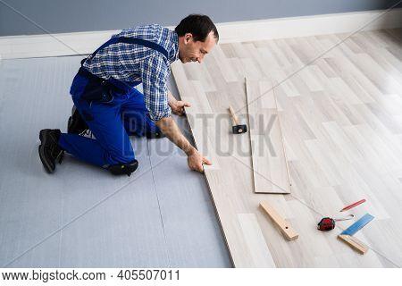 Hardwood Floor Renovation. Construction Worker Doing New Laminate Installation