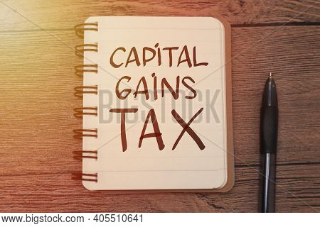 Capital Gains Tax, Text Words Typography Written On Book Against Wooden Background, Life And Busines