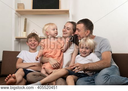 Happy Large Family At Home. Parents And Three Small Children Are Fun.