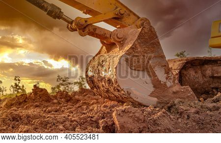 Dirt Metal Bucket Of Backhoe After Digging Soil. Backhoe Parked At Agricultural Land On Sunset Sky B