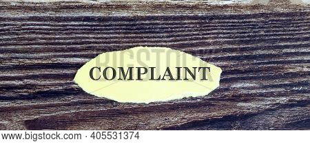 Business And Finance Concept. View Of Piece Of Paper Written Word Complaint On Wooden Background,