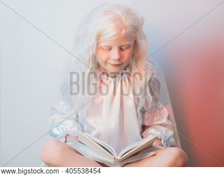 Kid Hobby. Story Time. Child Curiosity. Portrait Of Peaceful Adorable Blonde Albino Little Angel Gir