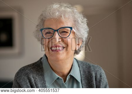 Happy retired senior woman wearing spectacles and relaxing at home. Carefree old woman wearing eyeglasses at home and smiling. Portrait of joyful grandmother with eyewear and toothy smile.