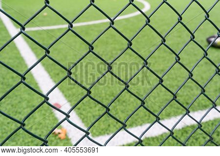 Fence Netting Close-up On A Background Of A Soccer Field.