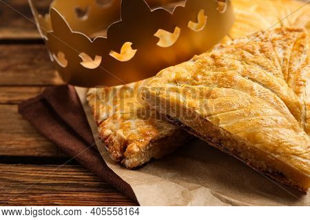 Traditional Galette Des Rois With Paper Crown On Wooden Table, Closeup
