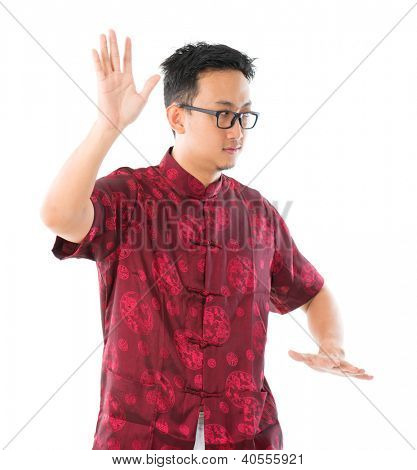 Southeast Asian Chinese male practicing tai chi, isolated on white background