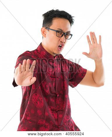 Southeast Asian Chinese man practicing kungfu, isolated on white background