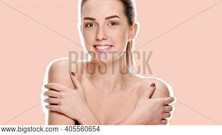 Portrait Of Smiling Young Woman Touching Perfect Smooth Face Skin On A Flesh Colored Background With