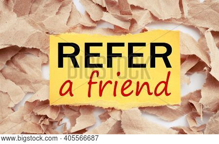Refer A Friend. Text On Yellow Paper On Torn Paper Background.